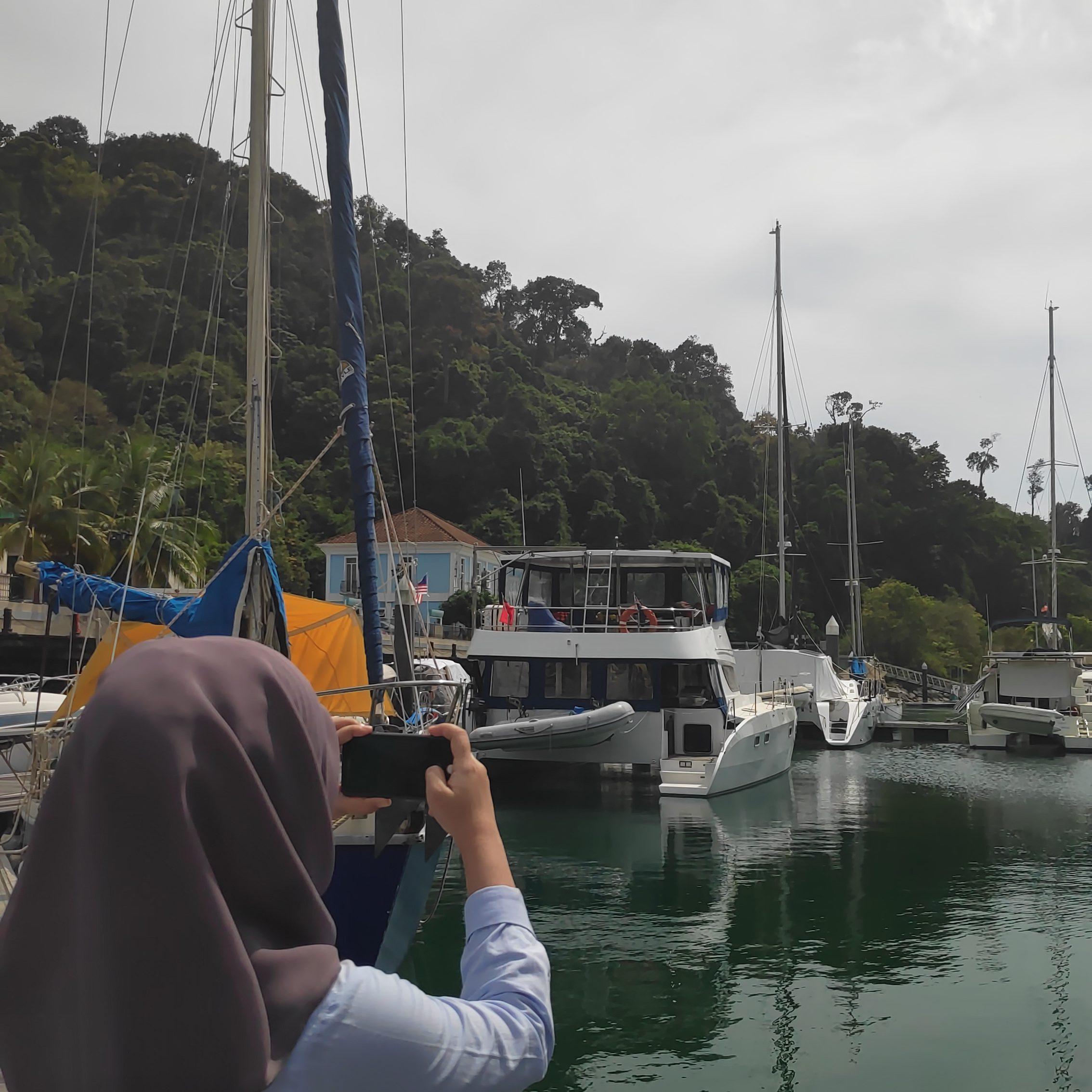 perempuan ambil gambar kapal